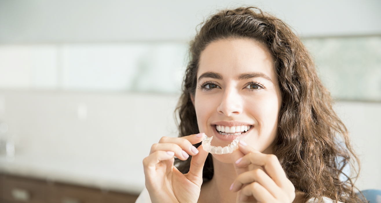 A Lady happily placing retainers in her mouth to keep her teeth straight.