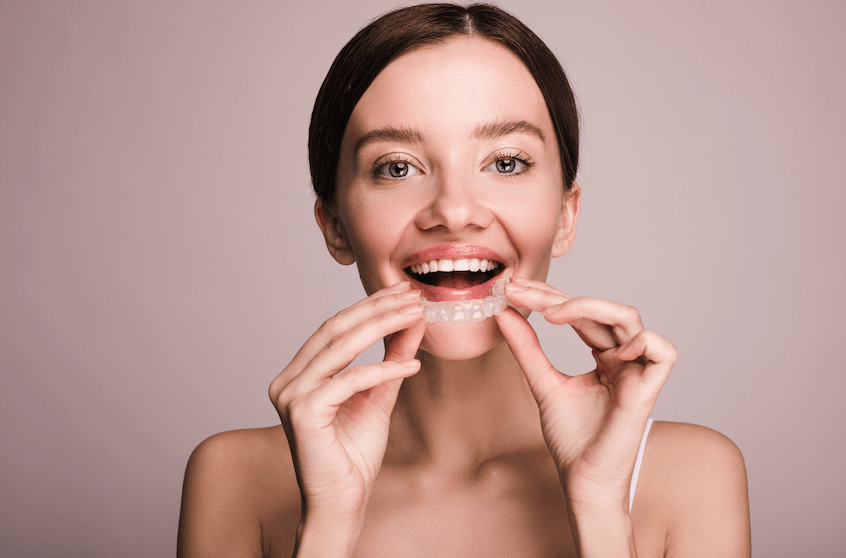 A lady with straight teeth who uses retainers every day.