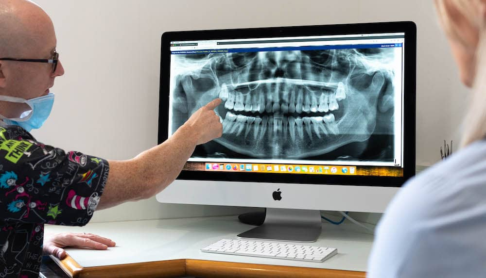 Anthony who the head Orthodontist at Oasis Orthodontics showing results to a patient after consultation.