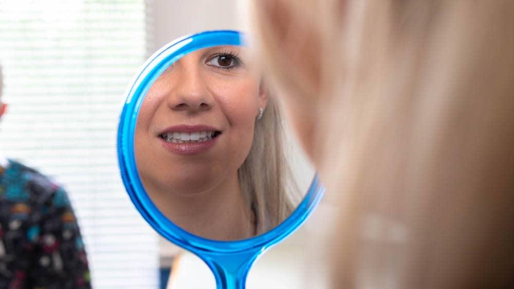 Roxanne looking in the mirror at her beautiful teeth.
